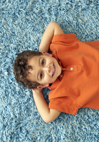 Boy Lying on Carpet --- Image by © Royalty-Free/Corbis